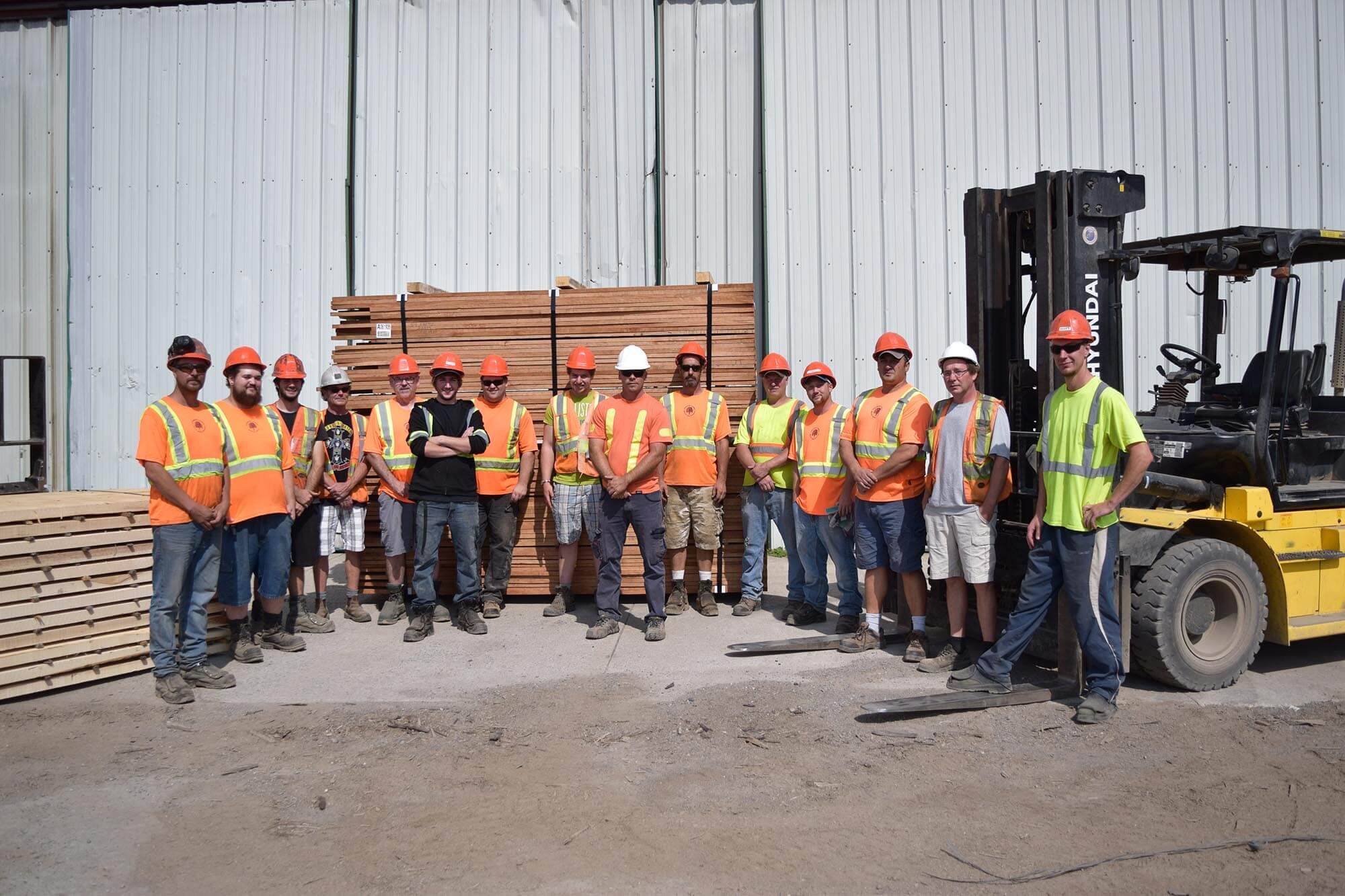 the townsend team posing outside wearhouse in front of large palettes of wood.