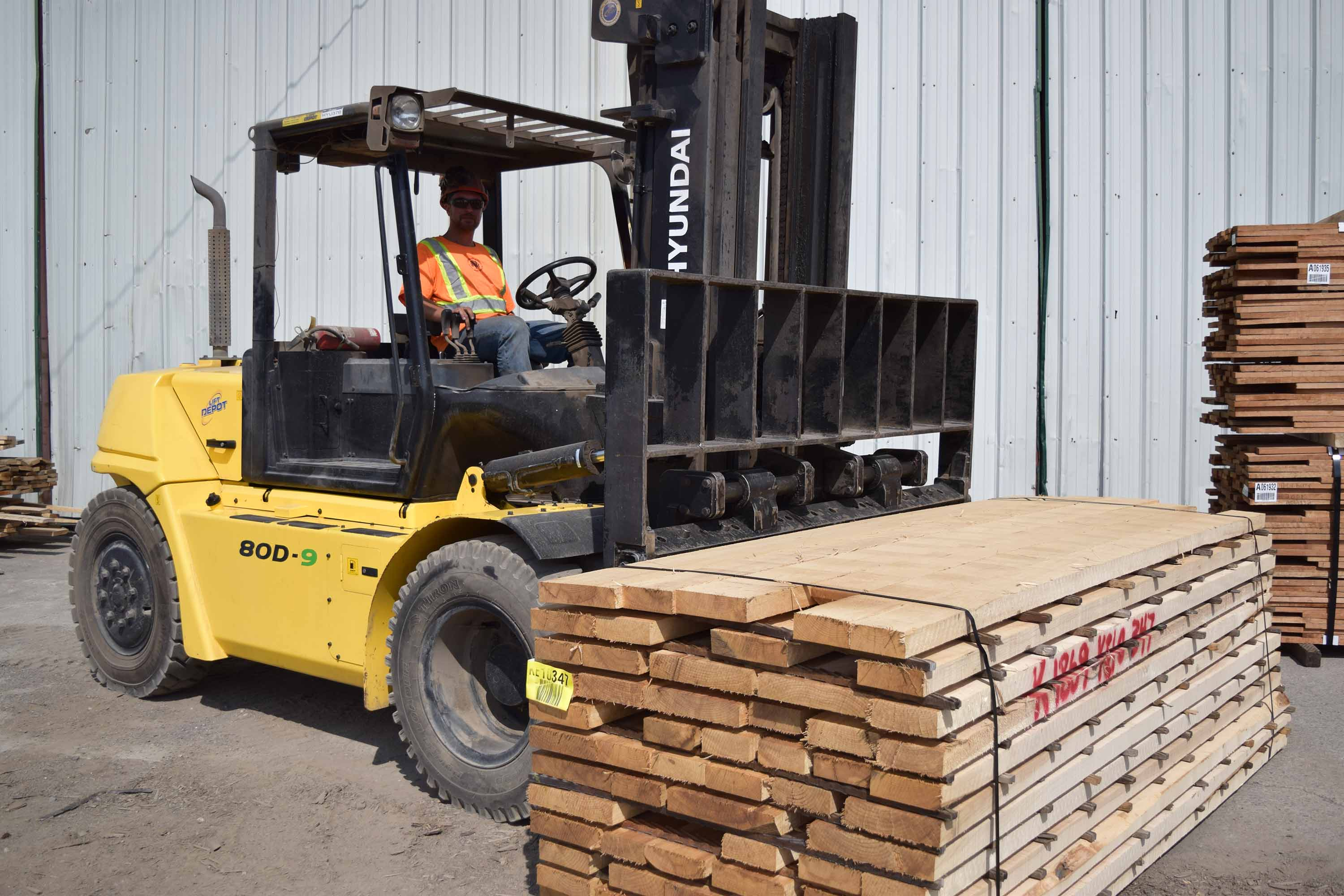 Forklift outside a wearhouse moving a large palette of lumber.