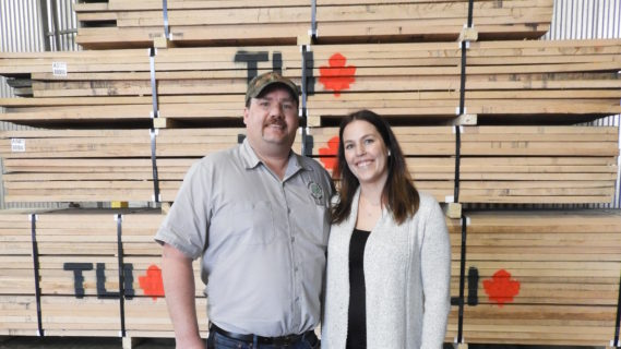 Man and women standing in front of a large pile of lumber with the TLI logo printed on the side.