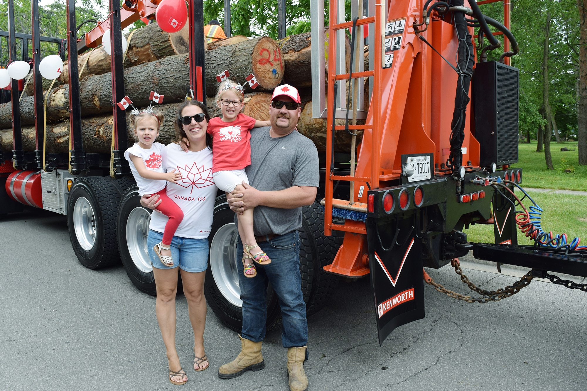 Man and women with 2 girls standing in front of Townsend lumber truck covered in red and white balloons for Canada Day.