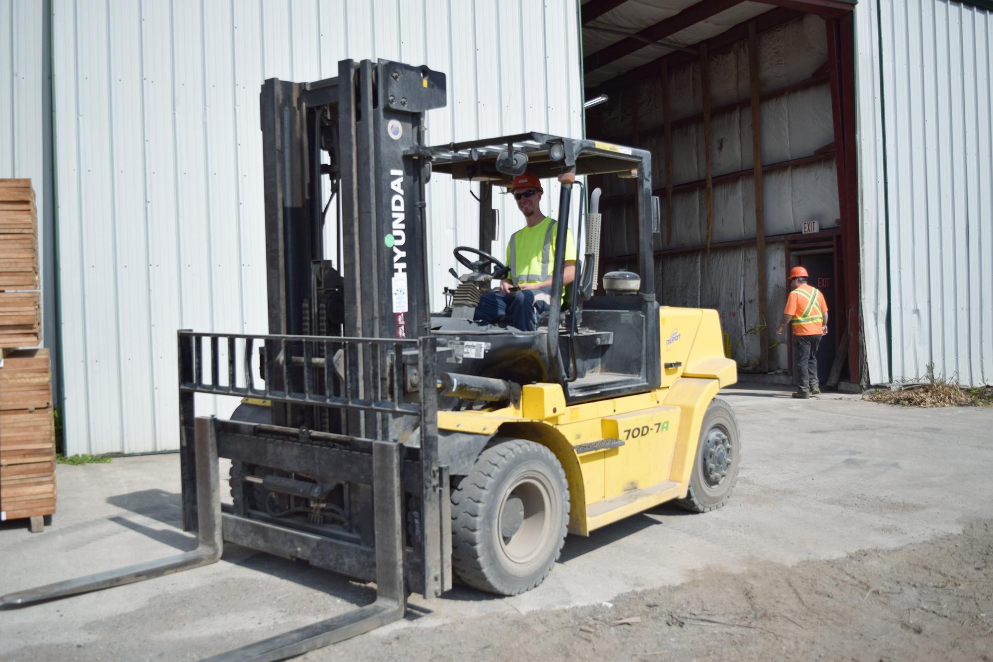 Man in construction uniform driving forklift