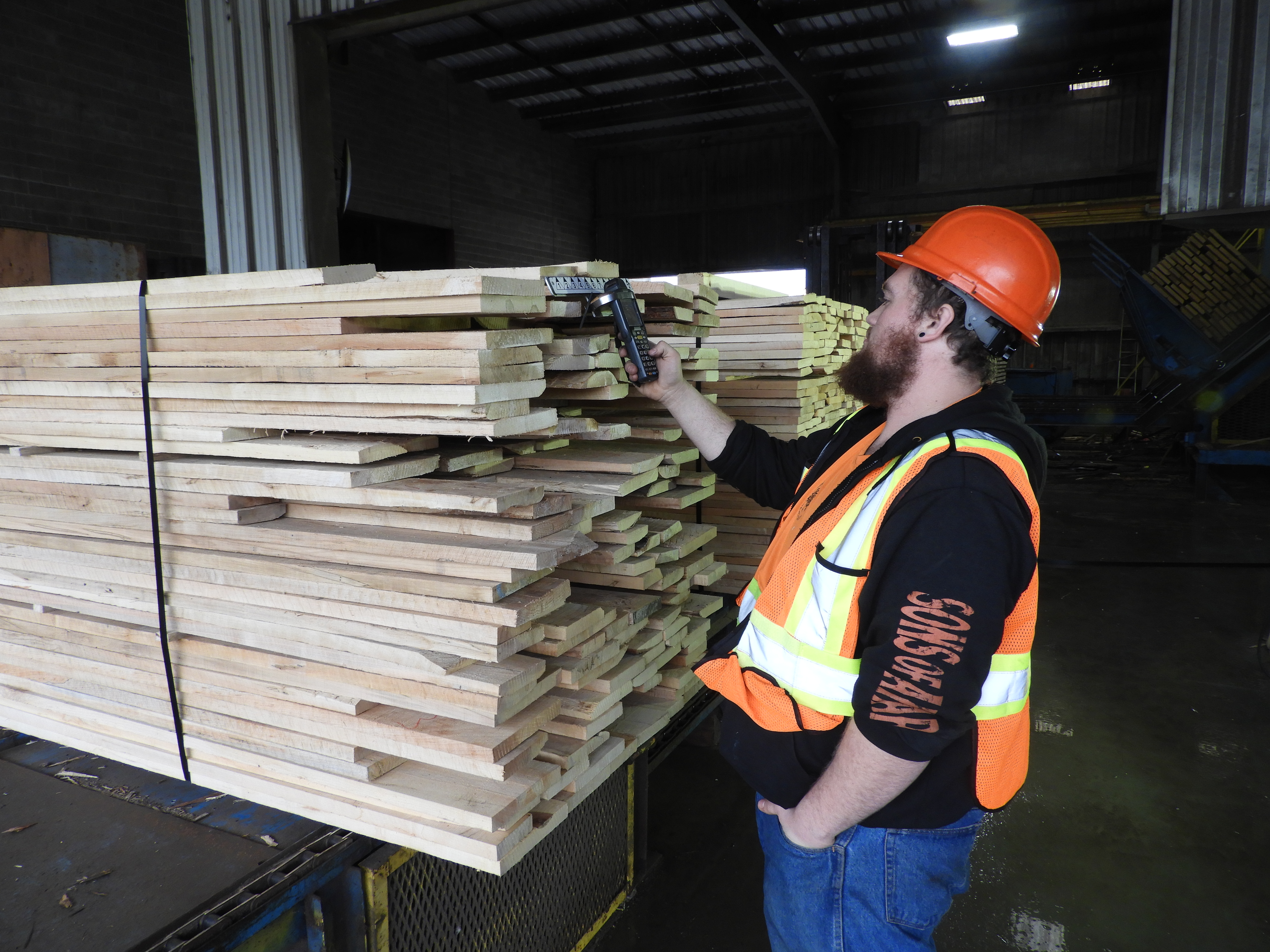 Man in construction uniform inspecting stacks of wood in wearhouse.