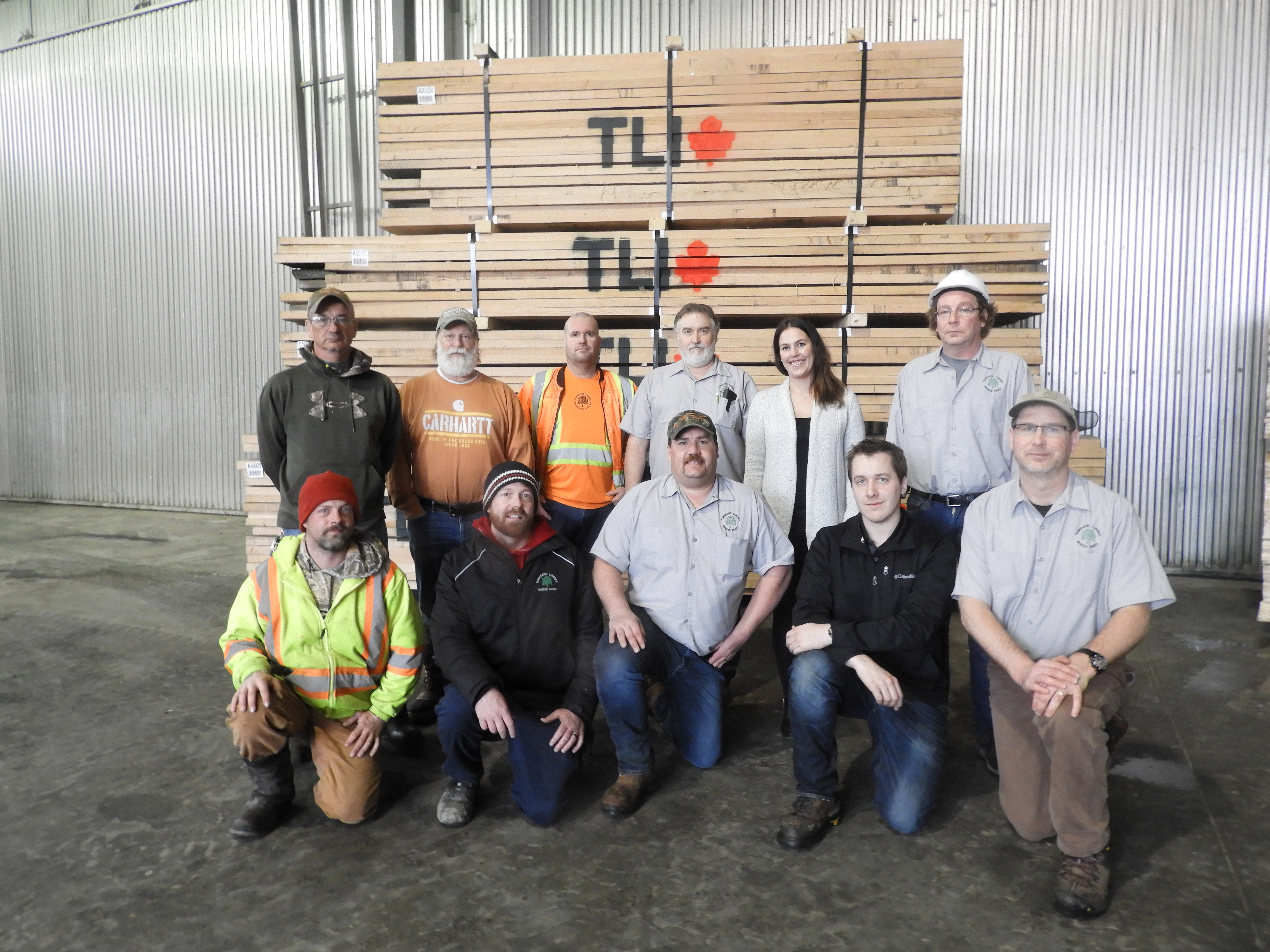 11 staff members posing in front of large pallet of wood with the TLI logo on it.