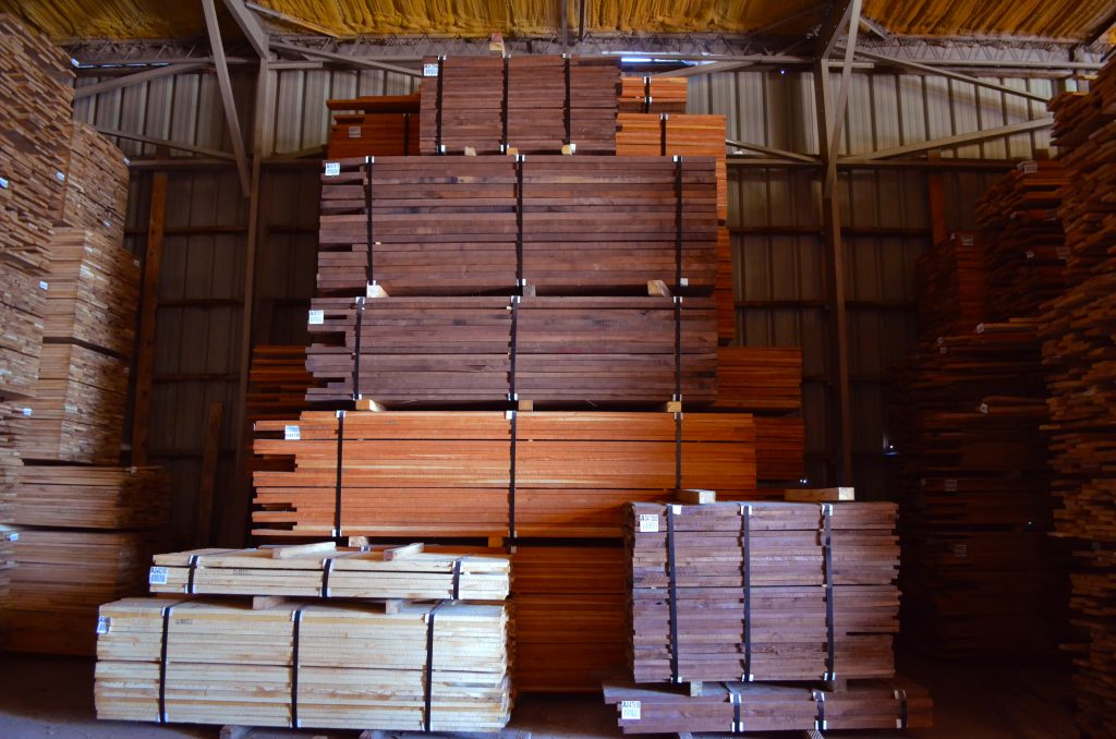 Dark wood panels stacked in concrete wearhouse.