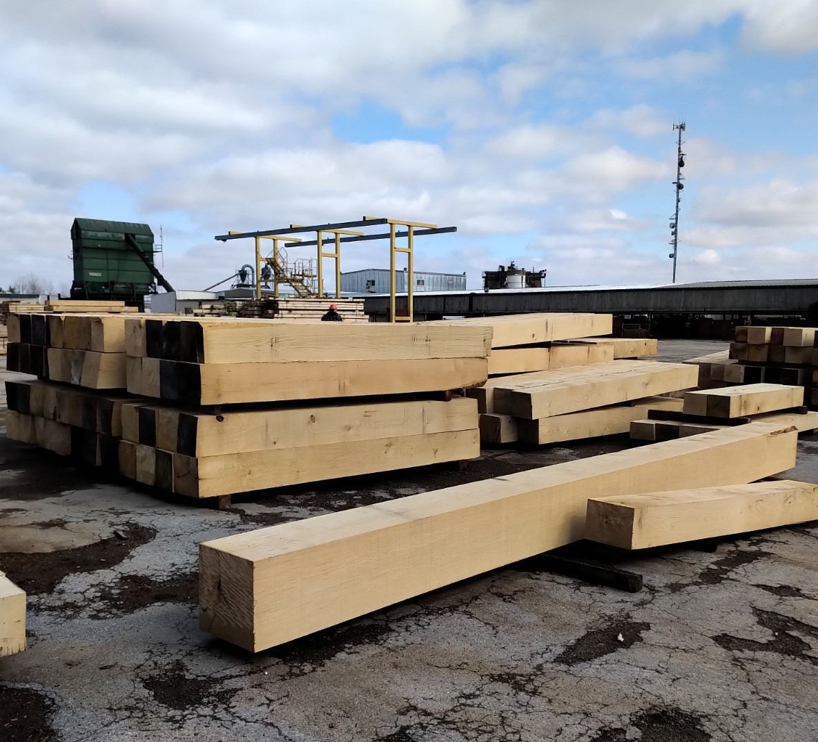 Large blocks of wood sitting in a concerte lot with machines in background.