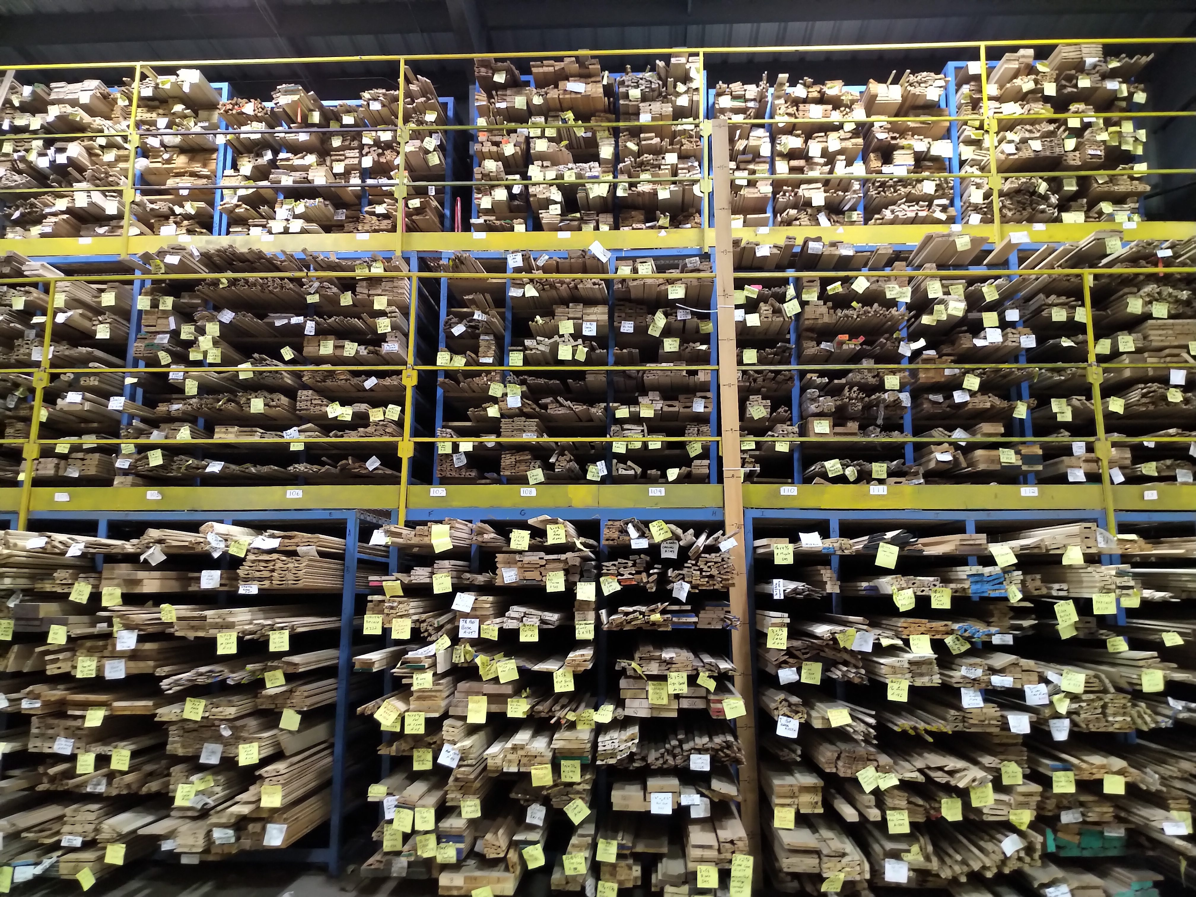 planks of wood organized by size and colour with yellow tags on the end. The wood is filled into cubbys.