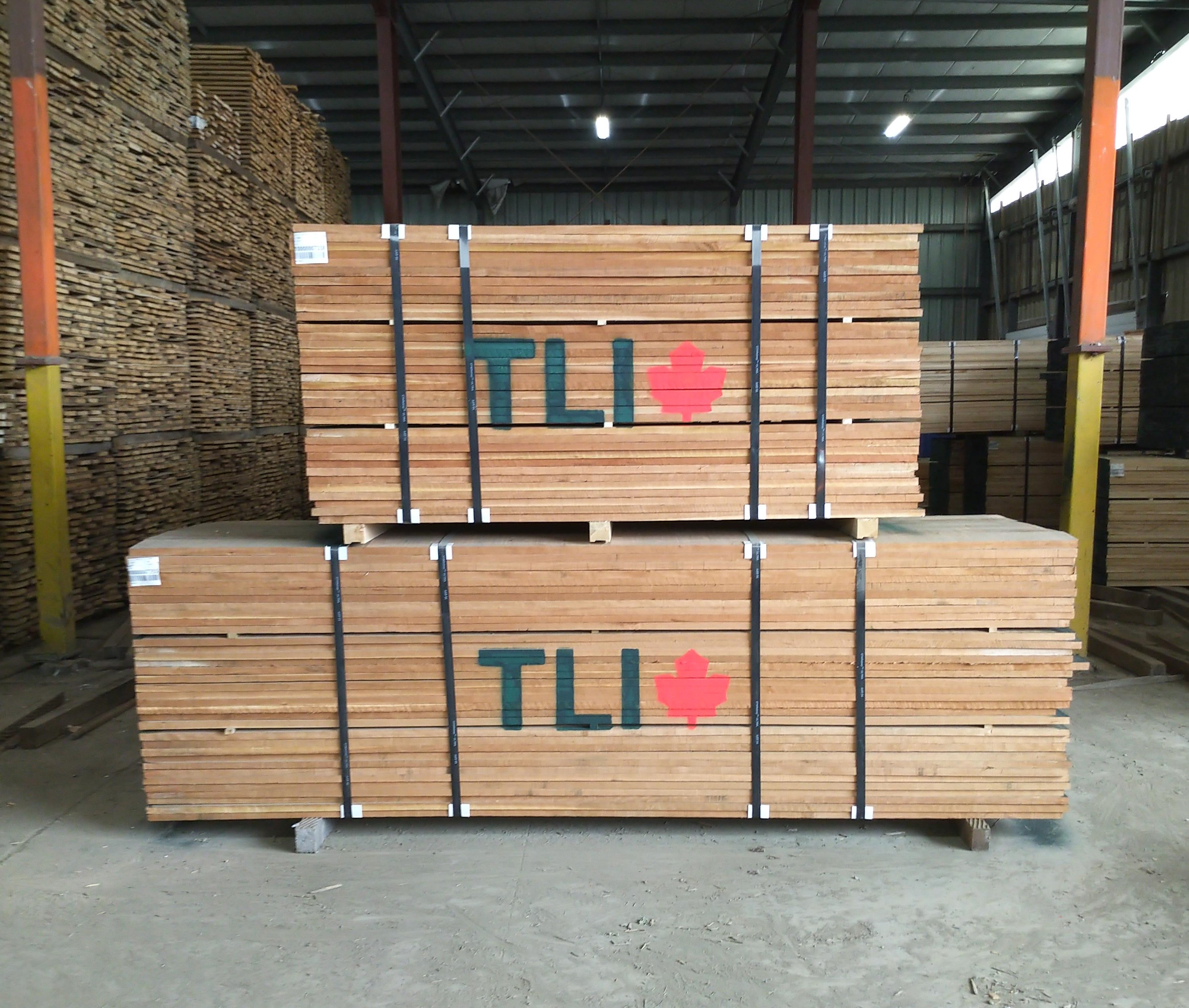 Large pallets of wood with the TLI logo painted on the side are sitting inside of a wearhouse