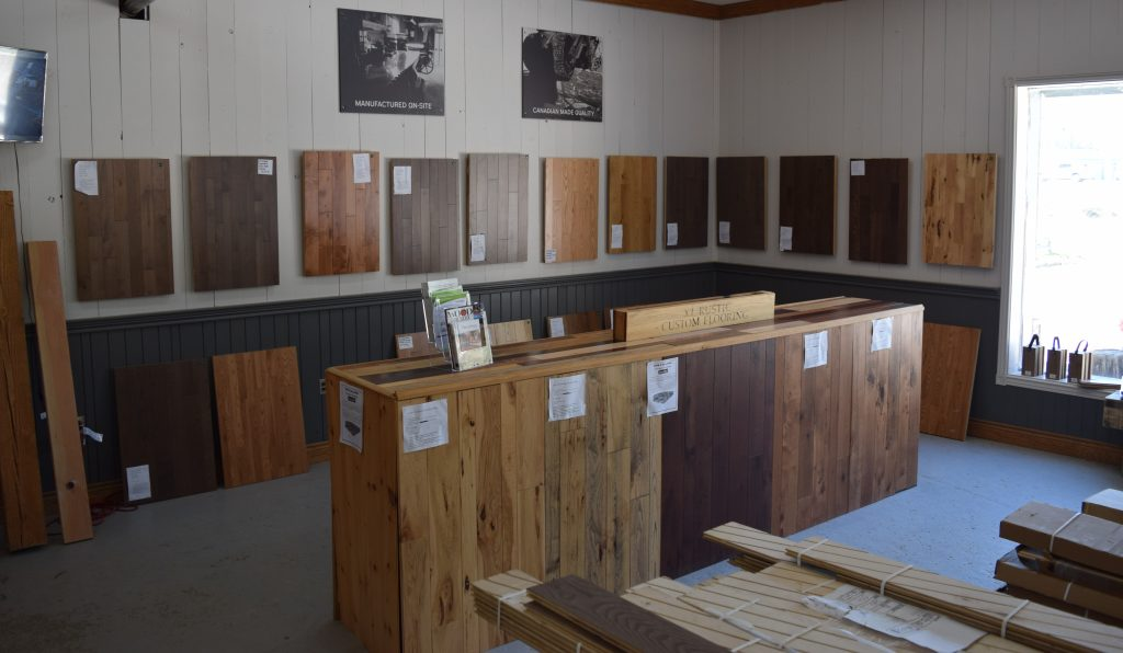 Inside a show room there are wood samples on the walls and an island in the middle with wood samples building the island.