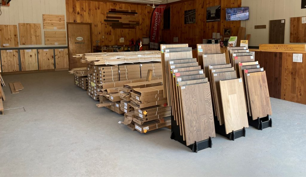 Inside a building, hardwood samples are displayed on the walls and boxes of wood are in the middle of the room.